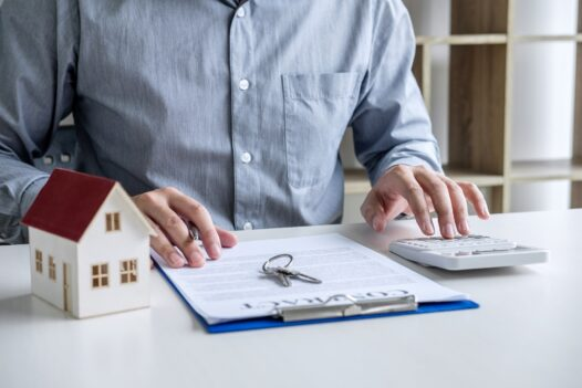 Businessman working doing finances and calculation cost of house, versus law conveyancing,